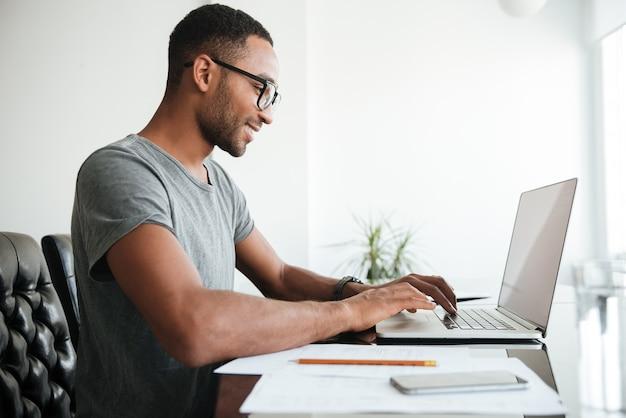 Felice giovane africano vestito con t-shirt gey e indossando occhiali utilizzando laptop e seduto al tavolo.