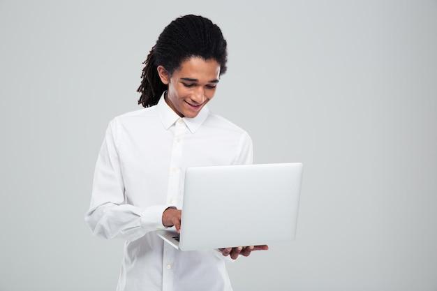 Uomo d'affari afroamericano felice che per mezzo del computer portatile sopra la parete grigia