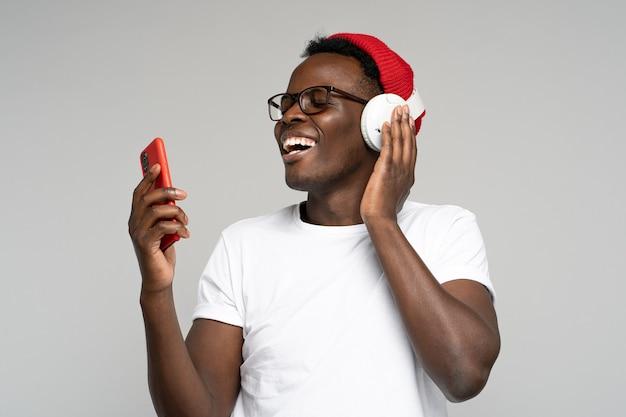 Felice l'uomo afro indossa le cuffie senza fili godendo l'ascolto di musica, balli, utilizzando smartphone