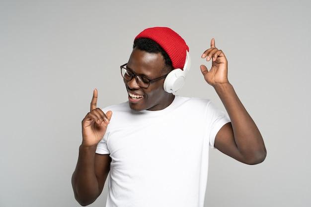 Felice l'uomo afro indossa le cuffie senza fili godendo l'ascolto di musica, ballando con le mani alzate