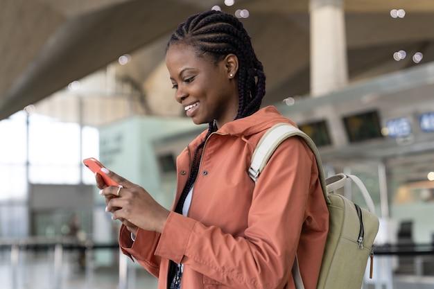 Felice donna afro controlla lo smartphone dopo il primo volo dopo il covid in aeroporto