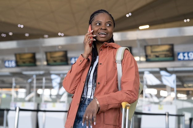 Felice donna afro che parla su smartphone dopo il primo volo dopo la fine del covid e l'arrivo in aeroporto