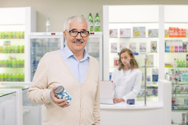 Felice uomo anziano in abbigliamento casual e occhiali con una grande bottiglia di pillole mentre si trova davanti alla telecamera contro l'assistente della farmacia
