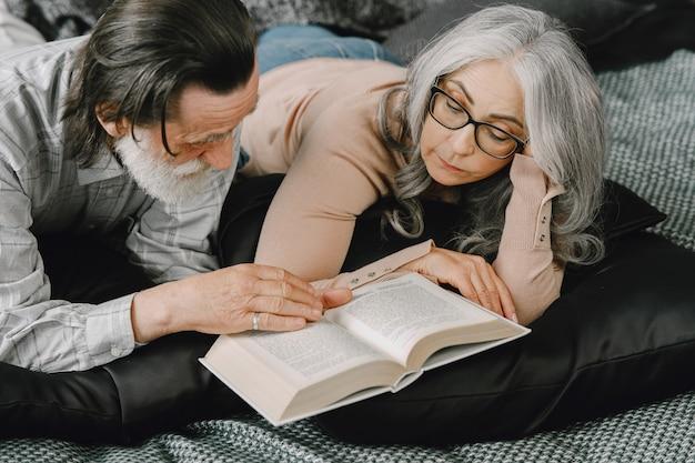 Coppia sposata invecchiata felice che si rilassa insieme a casa. libro di lettura delle coppie senior sul letto.