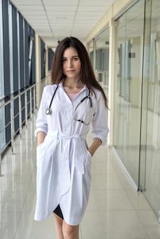 Felice solo giovane infermiera femminile nel corridoio dell'ospedale. concetto di medicina