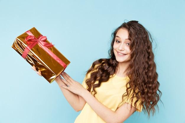 Felice donna stupita con scatola regalo d'oro.