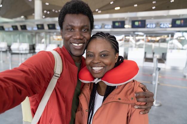 Felice coppia americana prendendo selfie al terminal dell'aeroporto pronto per tornare alla normalità