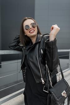 Felice hipster americano bella donna con sorriso bianco che indossa giacca di pelle alla moda con occhiali da sole vintage ed elegante borsa alla moda passeggiate in città. ritratto emotivo della modella