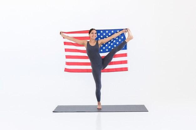 Felice donna americana che pratica yoga sul tappetino mentre sta in piedi con bandiera su sfondo bianco