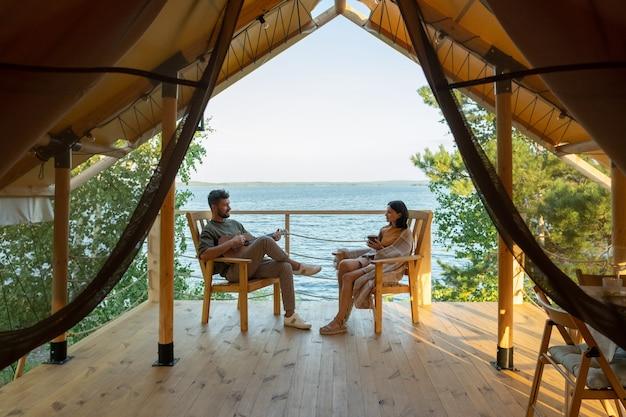 Felice coppia amorosa che si rilassa in poltrone di legno