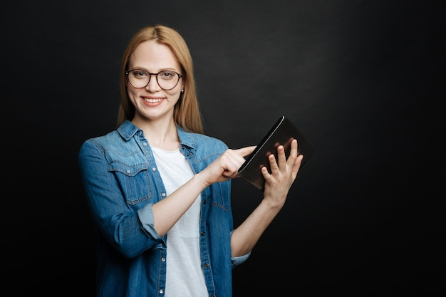 Felice divertita giovane donna che esprime positività e sorridente mentre utilizza tablet e in piedi in studio