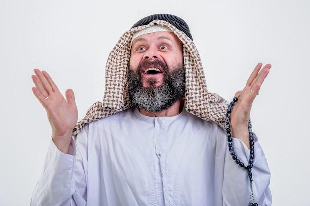 L'uomo arabo felice posa con le emozioni paralizzate su sfondo bianco