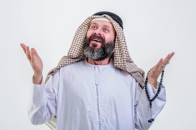 L'uomo arabo felice posa con le emozioni isolate su sfondo bianco