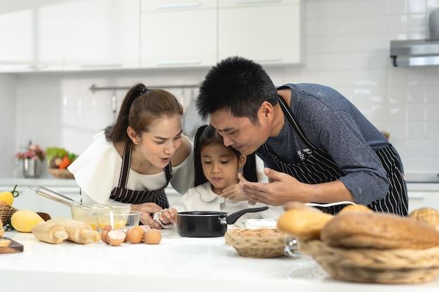 Famiglia felice dell'asia con la figlia che fa l'impasto preparando i biscotti da forno