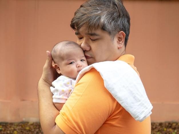 Padre felice dell'asia che tiene il suo bambino dolce neonato. il padre abbraccia il suo bambino con amore