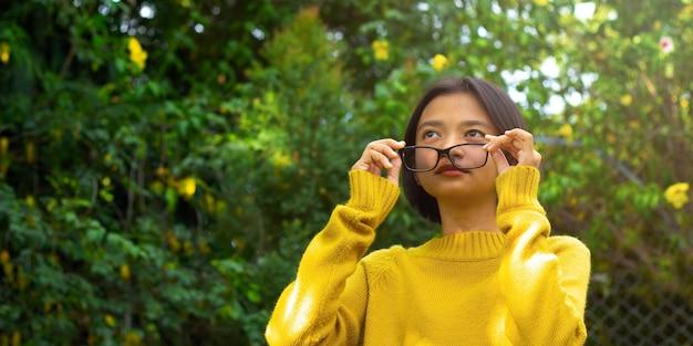 La ragazza felice dell'asia porta gli occhiali in natura.