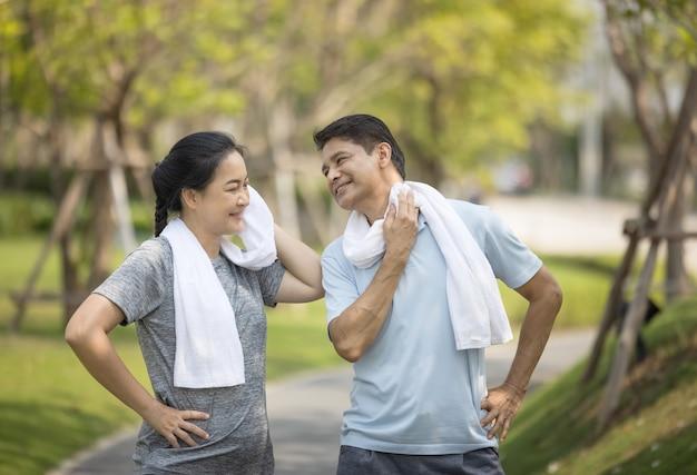 Coppie senior felici dell'asia che pareggiano all'aperto nel parco.