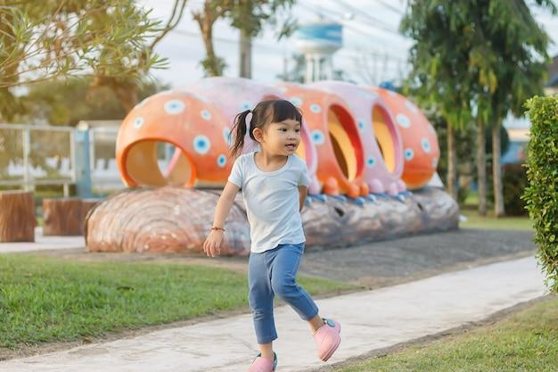Felice bambina asiatica correre o saltare e giocare nel campo del parco o giardino. lei sorride e ride.