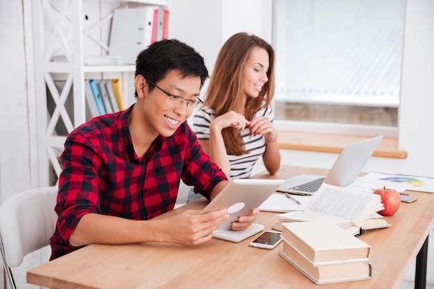Felice ragazzo asiatico con gli occhiali e vestito con una camicia in una gabbia e una ragazza caucasica vestita con una maglietta in una stampa a strisce che lavorano insieme per il progetto