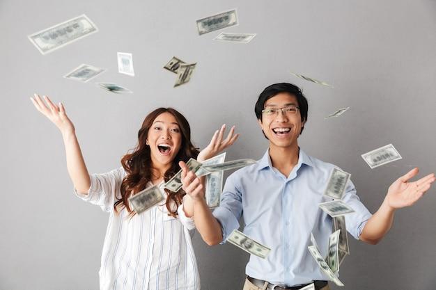 Coppie asiatiche felici di affari che stanno sotto la doccia delle banconote dei soldi isolata