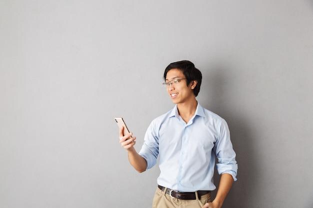 Felice uomo d'affari asiatico in piedi isolato, tenendo il telefono cellulare, agitando
