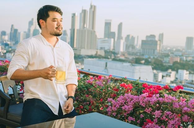 Uomo d'affari asiatico felice che sorride mentre beve birra al ristorante sul tetto