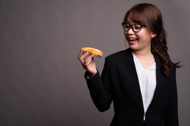 Happy asian imprenditrice azienda hot dog mentre sorride