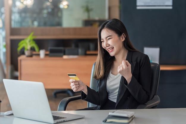 Felice imprenditrice asiatica shopping online utilizzando laptop e carte di credito in ufficio.