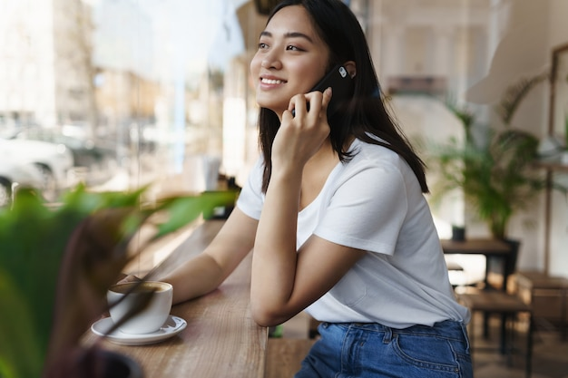 Donna candida asiatica felice che si siede nella caffetteria vicino alla finestra, guardando la strada mentre parla al telefono.