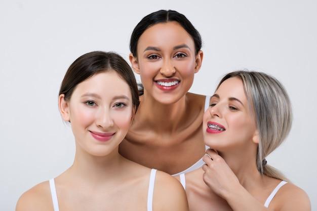 Felice ragazze asiatiche, caucasiche e africane con diversi tipi di pelle in mutandine bianche e camicia.