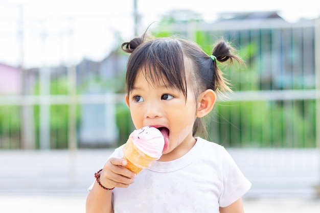 Ragazza asiatica felice del bambino che mangia un gelato alla vaniglia rosa. stagione estiva,