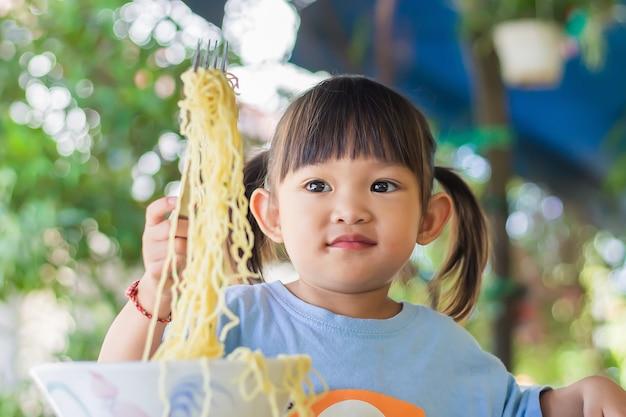 La ragazza asiatica felice del bambino gode di mangiare alcune tagliatelle da sola.