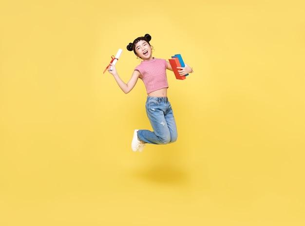 Ragazza asiatica felice del bambino che salta in su con il diploma e il libro isolato su priorità bassa gialla.