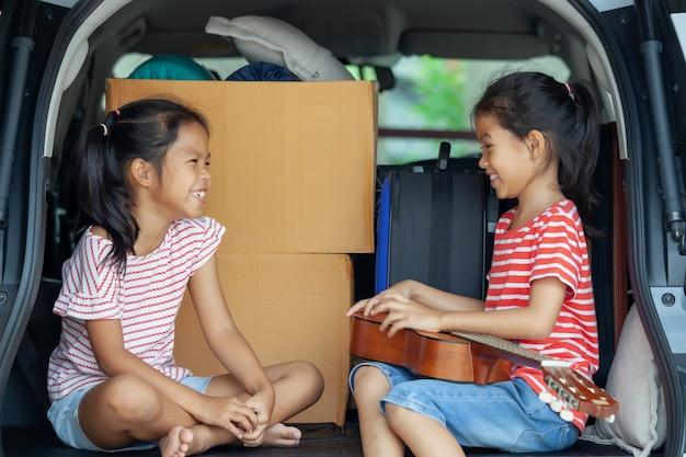 Ragazza asiatica felice del bambino che gioca chitarra e che canta una canzone con sua sorella in un bagagliaio di un'auto