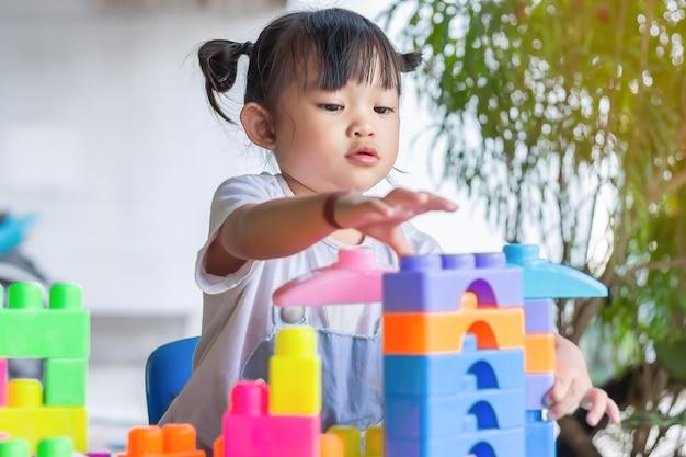Ragazza asiatica felice del bambino che gioca i giocattoli del blocco di plastica. concetto di apprendimento e istruzione. piccolo bambino sorridente.