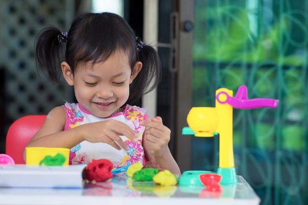 Ragazza asiatica felice del bambino che gioca giocattolo a casa