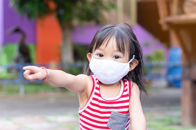Maschera sorridente e da portare della ragazza asiatica felice del bambino del tessuto. lei punta il dito verso il parco giochi.
