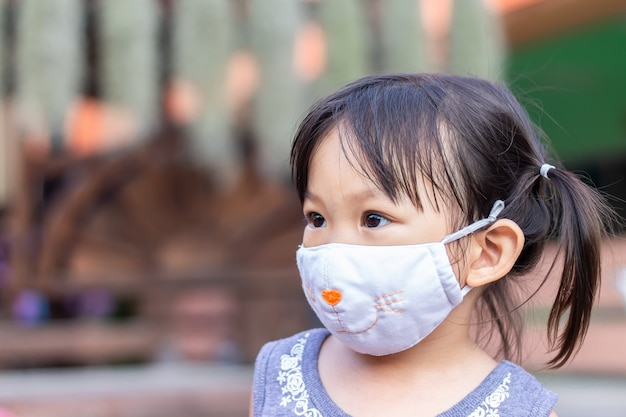 Ragazza asiatica felice del bambino che sorride e maschera da portare del tessuto. Foto Premium