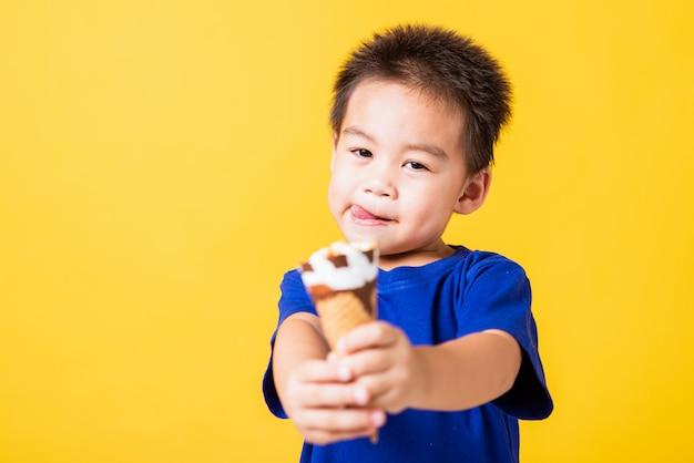 Il sorriso asiatico felice del ragazzino del bambino tiene e mangia il cono della cialda del gelato del cioccolato zuccherato