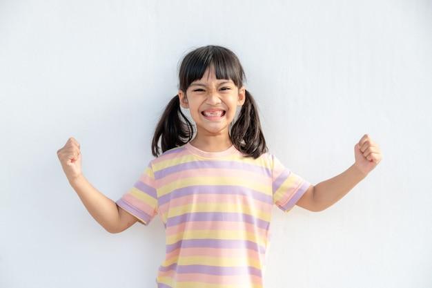 Bambini asiatici felici che mostrano le sue mani forti