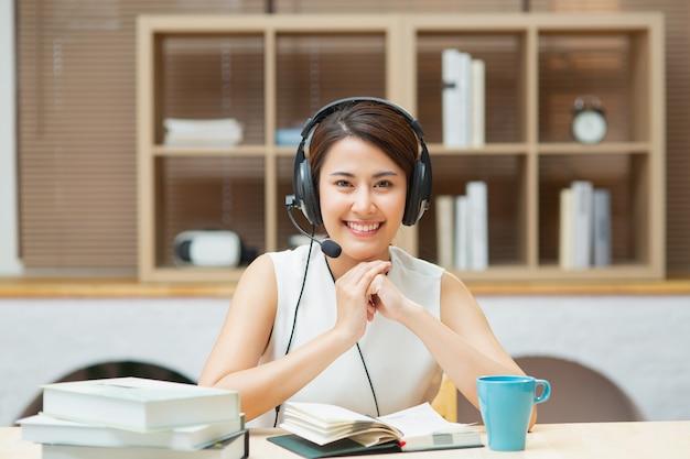 Donna cinese asiatica felice di affari con le cuffie che guarda l'obbiettivo che impara corso in linea
