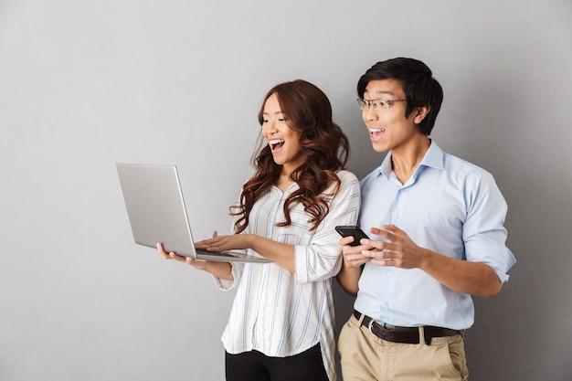 Felice coppia asiatica in piedi isolato, utilizzando il computer portatile, tenendo il telefono cellulare
