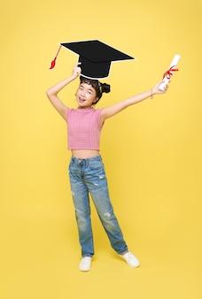 Felice studentessa asiatica carina con cappello di laurea e diploma isolato su sfondo giallo.