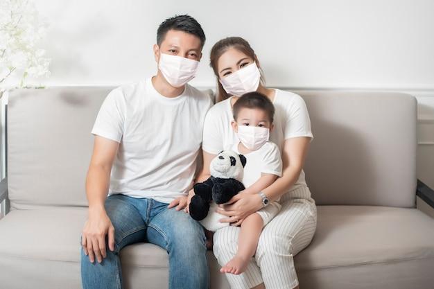 La famiglia asiatica felice sta indossando la maschera di soggiorno a casa