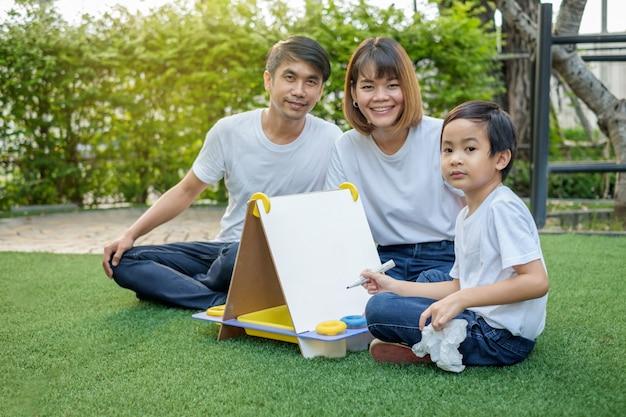 Famiglia asiatica felice nel cortile sull'erba