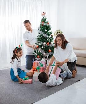 La famiglia asiatica felice decora insieme l'albero artificiale di natale a casa