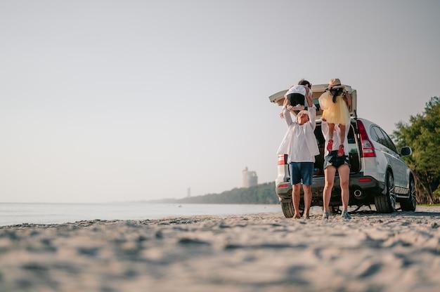 Felice famiglia asiatica che si gode una gita in spiaggia con la loro auto preferita genitori e bambini stanno viaggiando