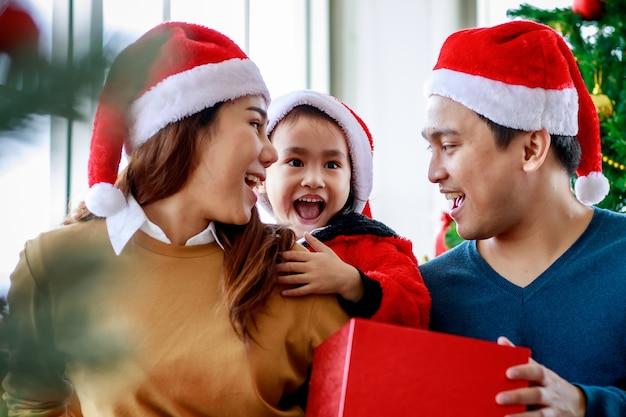 Felice famiglia asiatica padre madre e figlia indossa un maglione con cappello di babbo natale rosso e bianco sorridente ridendo tenendo presente confezione regalo prepararsi a unbox aprirlo insieme celebrando la vigilia di natale.