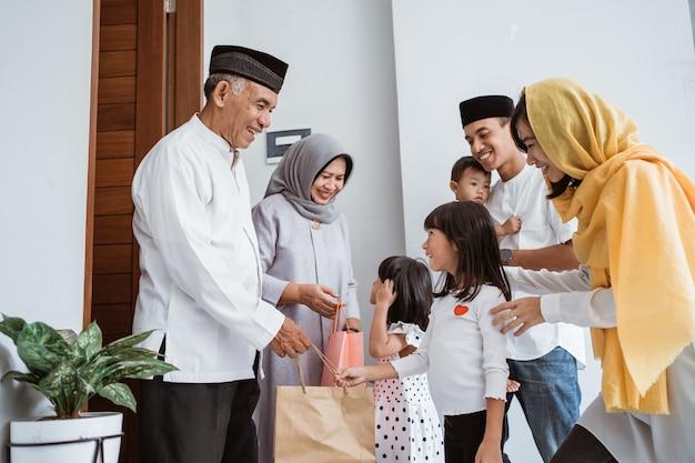 Famiglia asiatica felice che dà presente ai loro nonni musulmani durante la celebrazione di eid mubarak. regalo a sorpresa alla famiglia