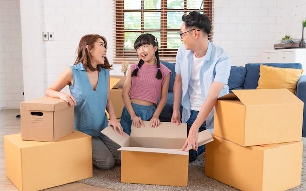 Una felice famiglia asiatica che tiene in mano una scatola di cartone si imbatte in una nuova casa. concetto di trasferimento